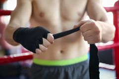 Young man wrapping hand with bandage. In boxing ring Royalty Free Stock Photography