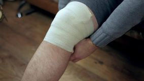 Young man wrapping his knee injury with elastic bandage closeup stock footage