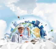 Creative inspiration of young writer. Young man writer in hat and eyeglasses pointing up while using typing machine at the table with flying papers and Earth Stock Photography