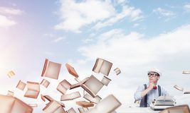 Creative inspiration of young writer. Young man writer in hat and eyeglasses using typing machine while sitting at the table among flying books with cloudy Royalty Free Stock Photo