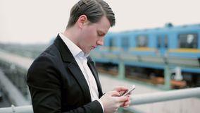 Young man writes messages on his mobile phone.