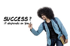 Young man writes success it depends on you word. Young afro man writing success it depends on you word on whiteboard while holding book, isolated on white Royalty Free Stock Photos