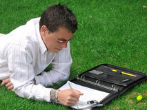 Young Man Writing. Young, casual man working, stuyding while lying in the grass stock photography