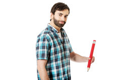 Young man writing with big red pencil. Royalty Free Stock Photo