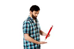 Young man writing with big red pencil. Royalty Free Stock Images