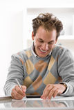 Young man writing at desk Stock Photography
