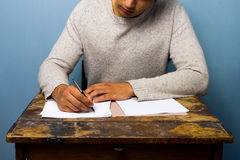 Young man writing at desk Royalty Free Stock Image