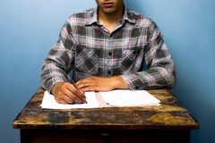 Young man writing at desk Stock Image