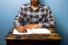 Young man writing at desk Stock Image