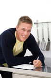 Young man writing down recipe Stock Photography