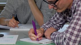 Young man writing in his textbook while studying stock photo