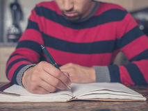 Young man writing in kitchen Royalty Free Stock Photos