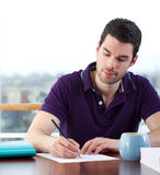 Young man writing a letter. Attractive young man writes a letter by hand Stock Photography