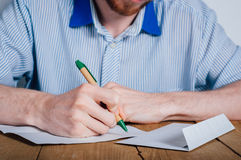 Young man writing letter Stock Image