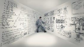 Math formulas on walls. Young man writing math and physical formulas on walls Stock Photo