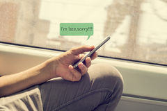 Young man writing a message to apologize. Closeup of a young caucasian man writing a text message with his smartphone to apologize his delay, with the text I am royalty free stock photography