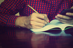 Young man writing on notebook about cost and holing phone using Royalty Free Stock Photo