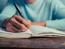 Young man writing in notebook Stock Image