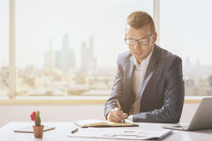 Young man writing in notepad Stock Images