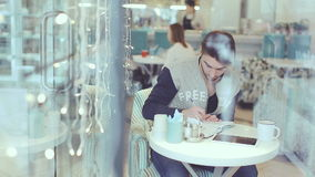 Young man writing in notepad in cafe, static shot stock footage