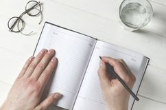 Man hands writing notes to the notebook on wooden table in home office royalty free stock images
