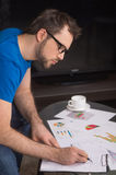 Young man writing on paper in glasses. Stock Photos