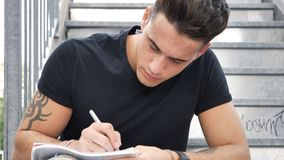 Young man writing on paper sheet with pen Royalty Free Stock Image