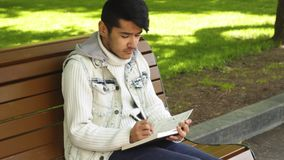 Young man writing something in notebook stock footage