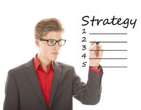Young man writing strategy on white isolated background Royalty Free Stock Images