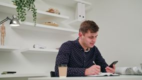 A young man writing and using a phone indoors. Medium Dolly shot stock footage