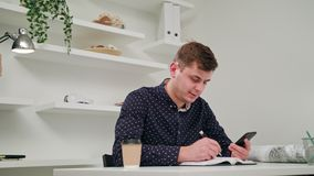 A young man writing and using a phone indoors. Medium Dolly shot stock video footage
