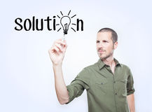 Young man writing the word solution royalty free stock image