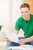 Young man writting and holding paper. Royalty Free Stock Photography
