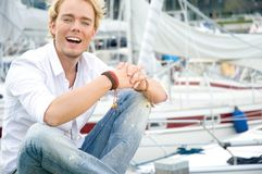 Young man at a yachtclub. Young man sitting near some yachts at a yachtclub Stock Images