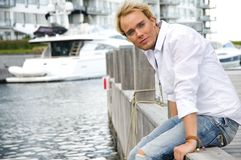 Young man at a yachtclub. Young man sitting near some yachts at a yachtclub Royalty Free Stock Image