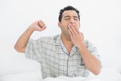 Young man yawning in bed Royalty Free Stock Photo