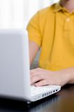 Young man in yellow shirt types on notebook Royalty Free Stock Images