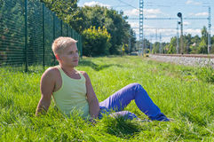 Young man in yellow sitting on the green grass Royalty Free Stock Photo