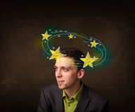 Young man with yellow stars circleing around his head Royalty Free Stock Photography