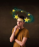 Young man with yellow stars circleing around his head Royalty Free Stock Images