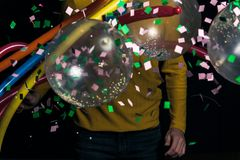 Young man in yellow sweater with balloons partying. For new year royalty free stock image