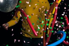Young man in yellow sweater with balloons partying. For new year stock photos