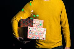 Young man in yellow sweater hold presents stock photo