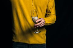 Young man in yellow sweater pours champagne in a glass royalty free stock photography