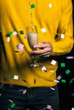 Young man in yellow sweater pours champagne in a glass royalty free stock photo