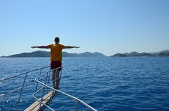 Young man in yellow t-shirt and red shorts on the bow of yacht outstretched arms like bird wings on a summer sunny day. Back view stock photos