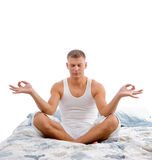 Young man in yoga meditation in bed Stock Image