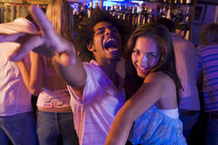 Young man and young woman dancing in a nightclub. Looking at camera Royalty Free Stock Photography