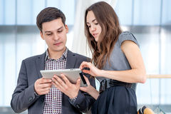 A young man and young woman standing on the stairs. A young men and young women standing on the stairs businessmen and solve problems on the tablet. Young people Stock Images