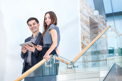 A young man and young woman standing on the stairs  Royalty Free Stock Photos
